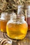 La miel en un vidrio sacude en un fondo rústico de madera Foto de archivo libre de regalías