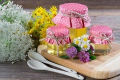 La miel en un vidrio sacude, y cazo de la miel con las flores salvajes Imagen de archivo