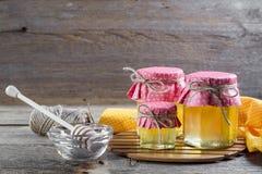 La miel en un vidrio sacude, y cazo de la miel con las flores salvajes Imagenes de archivo
