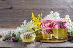 La miel en un vidrio sacude, y cazo de la miel con las flores salvajes Imágenes de archivo libres de regalías