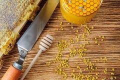 La miel fresca en el peine y las herramientas del apicultor en un queso de cerdo vooden el fondo Endecha plana y visión superior imagenes de archivo