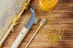 La miel fresca en el peine y las herramientas del apicultor en un queso de cerdo vooden el fondo Endecha plana y visión superior foto de archivo