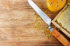 La miel fresca en el peine y las herramientas del apicultor en un queso de cerdo vooden el fondo Endecha plana y visión superior foto de archivo libre de regalías