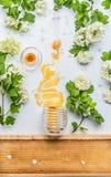 La miel mancha del tarro con las flores y el peine de la miel en el fondo blanco Fotos de archivo