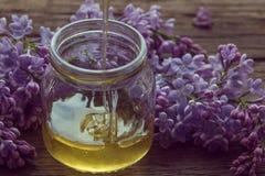 La miel orgánica vierte un tarro de cristal, envuelto en una flor de la primavera, Foto de archivo libre de regalías