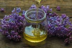 La miel orgánica vierte un tarro de cristal, envuelto en una flor de la primavera, Fotografía de archivo libre de regalías