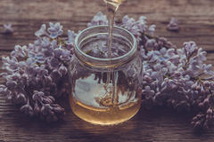 La miel orgánica vierte un tarro de cristal, envuelto en una flor de la primavera, Imágenes de archivo libres de regalías