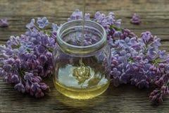La miel orgánica vierte un tarro de cristal, envuelto en una flor de la primavera, Imagenes de archivo