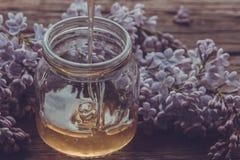 La miel orgánica vierte un tarro de cristal, envuelto en una flor de la primavera, Imagen de archivo libre de regalías