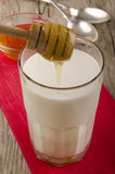 La miel se vierte en un vidrio de leche caliente Fotografía de archivo