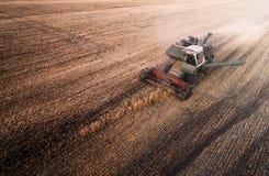 La mietitrice che lavora nel campo e falcia il grano l'ucraina Siluetta dell'uomo Cowering di affari Fotografie Stock