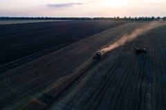 La mietitrice che lavora nel campo e falcia il grano l'ucraina Siluetta dell'uomo Cowering di affari Immagine Stock