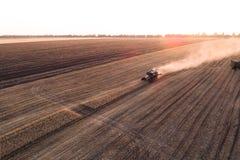 La mietitrice che lavora nel campo e falcia il grano l'ucraina Siluetta dell'uomo Cowering di affari Immagini Stock