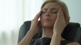 La migraine gêne la jeune femme travaillante d'affaires, le travail stressant et la date-butoir banque de vidéos