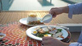 La minestra del gamberetto è un piatto tailandese con un gusto acido e piccante l'uomo sta mangiando Tom Yam ad una tavola dallo  fotografia stock