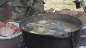 La minestra del pesce fresco sta bollendo su un fuoco mettendo un certo pesce in una ciotola stock footage