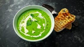 La minestra della menta e di piselli dolci verde con l'acquerugiola dell'olio d'oliva e della crema è servito con i pani tostati  Fotografia Stock