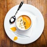 La minestra della zucca con i semi di zucca e della crema in una ciotola bianca sopra corteggia Immagini Stock Libere da Diritti