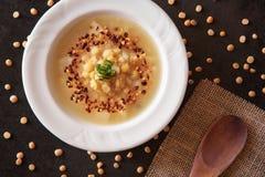 La minestra di piselli spaccata è decorata con i fiocchi del peperone su ston nero immagini stock