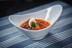 La minestra russa tradizionale Solyanka con carne, sottaceti, ha affettato le salsiccie, le olive ed il limone in piatto bianco P Immagini Stock