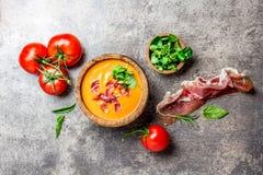 La minestra spagnola Salmorejo del pomodoro è servito in ciotola di legno verde oliva con il serrano del jamon del prosciutto su  Fotografia Stock