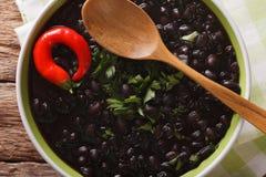 La minestra spessa del fagiolo nero con i peperoncini si chiude su in una ciotola fotografia stock