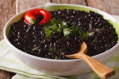 La minestra spessa del fagiolo nero con i peperoncini si chiude su in una ciotola fotografie stock