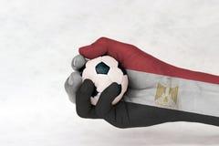La mini bola del fútbol en la bandera de Egipto pintó la mano en el fondo blanco Concepto de deporte o el juego en manija o mater imágenes de archivo libres de regalías