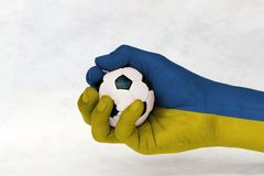 La mini boule du football dans le drapeau de l'Ukraine a peint la main sur le fond blanc photographie stock