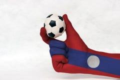 La mini boule du football dans la main peinte par drapeau du Laos, la tiennent avec le doigt deux sur le fond blanc photos stock