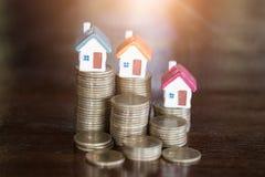 La mini casa sulla pila di monete, di soldi e di casa, investimento di bene immobile, risparmia i soldi con la moneta della pila, fotografia stock