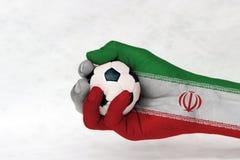 La mini palla di calcio in bandiera dell'Iran ha dipinto la mano su fondo bianco fotografia stock