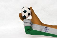 La mini palla di calcio in mano dipinta bandiera dell'India, la tiene con il dito due su fondo bianco fotografia stock