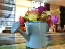 La mini regadera adorna en la tabla con las flores Foto de archivo