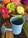 La mini regadera adorna en la tabla con las flores Fotos de archivo