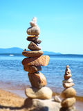 La miniature a brouillé l'effet de deux cairns de tour de roche sur la plage sablonneuse et le lac photographie stock libre de droits