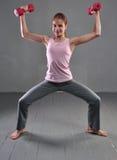 La mirada abajo de muchacha juguetona adolescente está haciendo ejercicios para convertirse con los músculos de las pesas de gimn Fotografía de archivo libre de regalías