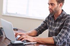 La mirada caucásica joven del estudiante alimentó-para arriba con el trabajo sobre su ordenador portátil Imagen de archivo libre de regalías
