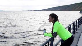 La mirada de la mujer del deporte por el mar toma una rotura en el terraplén de la ciudad que sostiene la botella de agua almacen de video