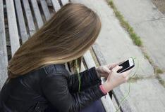 La mirada hermosa joven de la muchacha y la música que escucha en su teléfono móvil en los estadios viejos bench Fotos de archivo