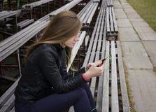 La mirada hermosa joven de la muchacha y la música que escucha en su teléfono móvil en los estadios viejos bench Imagen de archivo libre de regalías