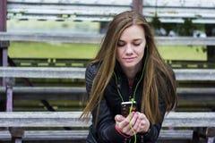 La mirada hermosa joven de la muchacha y la música que escucha en su teléfono móvil en los estadios viejos bench Fotos de archivo libres de regalías