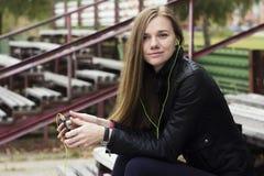 La mirada hermosa joven de la muchacha y la música que escucha en su teléfono móvil en los estadios viejos bench Imágenes de archivo libres de regalías