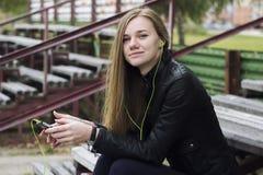 La mirada hermosa joven de la muchacha y la música que escucha en su teléfono móvil en los estadios viejos bench Imagen de archivo