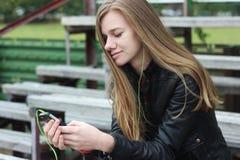 La mirada hermosa joven de la muchacha y la música que escucha en su teléfono móvil en los estadios viejos bench Foto de archivo libre de regalías