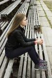 La mirada hermosa joven de la muchacha y la música que escucha en su teléfono móvil en los estadios viejos bench Imagenes de archivo