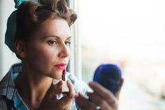 La mirada modela vistió las pinturas de la mujer sus labios con el lápiz labial rojo Fotos de archivo