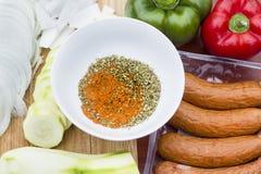 La miscela delle erbe e delle spezie sta stando su una tavola in una ciotola circondata dai peperoni, dalle cipolle e dallo zucch fotografie stock