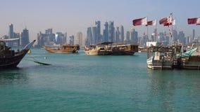 La miscela delle età Vista sull'orizzonte moderno della città di Doha Colpo di giorno, Qatar, barche di legno tradizionali di Med video d archivio