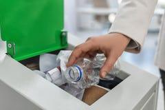 La mise de femme a utilisé la bouteille en plastique dans la poubelle dans le bureau, plan rapproché Recyclage des déchets photo libre de droits